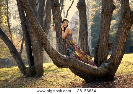 Hippie Girl on a tree branch in autumn
