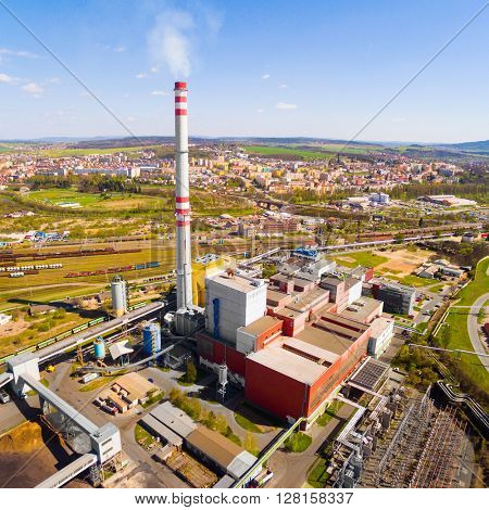 Aerial view of modern combined heat and power plant. Fuming chimney with sulphur removal unit. Heavy industry from above. Power and fuel generation in Czech Republic, European Union.