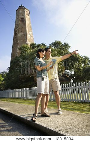 Mid-adult Caucasian couple sightseeing with lighthouse in background at Bald Head Island, North Carolina.