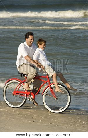 Caucasian mid-adult man riding bicycle on beach with pre-teen boy on handlebars.