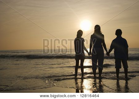 Caucasian mid-adult mother and tenage kids standing silhouetted on beach at sunset.