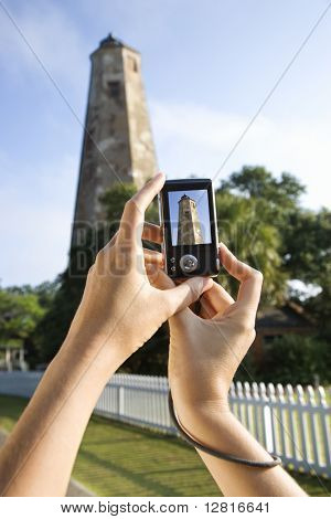 Close up of Caucasian woman's hands holding digital camera and photographing lighthouse at Bald Head Island, North Carolina.