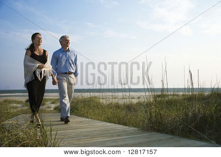 Caucasian mid-adult couple holding hands and walking down walkway at beach.