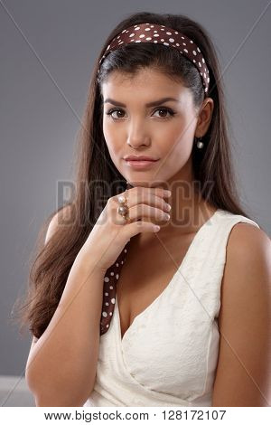 Portrait of confident young attractive woman, looking at camera hand on chin.
