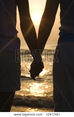 Caucasian mid-adult mother and teenage daughter standing on beach at sunset holding hands.