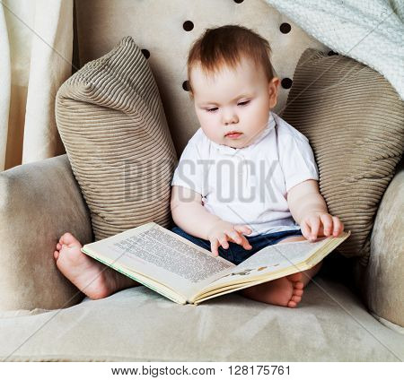 adorable baby reading a book in the chair at home
