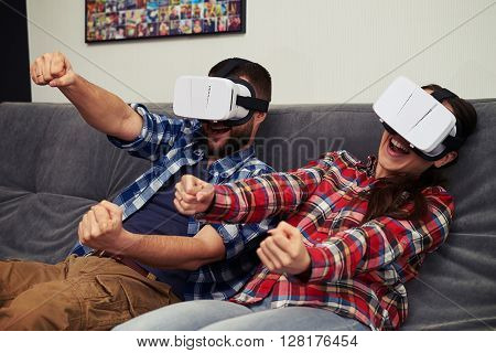 A young man and woman in casual clothes playing racing game using virtual reality headset