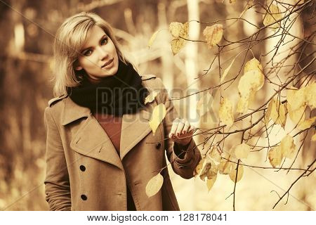 Happy beautiful fashion woman walking in autumn forest. Female fashion model in beige classic coat outdoor