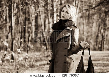 Young blond fashion woman with handbag walking in autumn forest. Female fashion model in classic coat outdoor