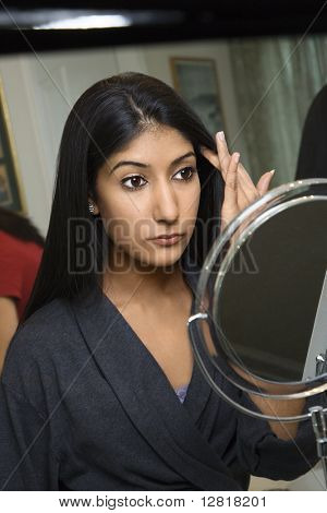 Close up of Asian/Indian young woman looking in mirror primping.