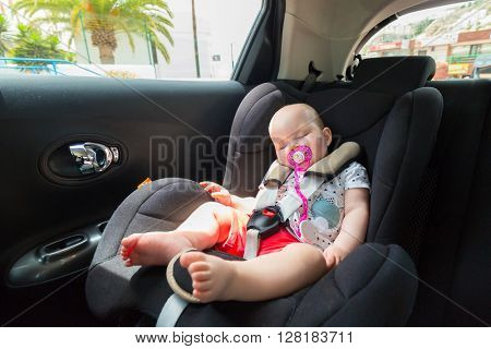 Cute baby girl is sleeping in the car on child safety seat