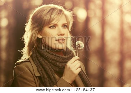 Happy young fashion woman walking in autumn forest. Female blond fashion model in classic beige coat outdoor
