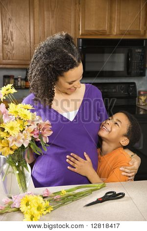 Portrait of expecting mother and son in kitchen.