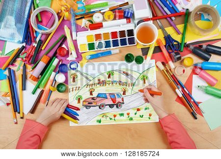 red car on countryside and steam train child drawing, top view hands with pencil painting picture on paper, artwork workplace