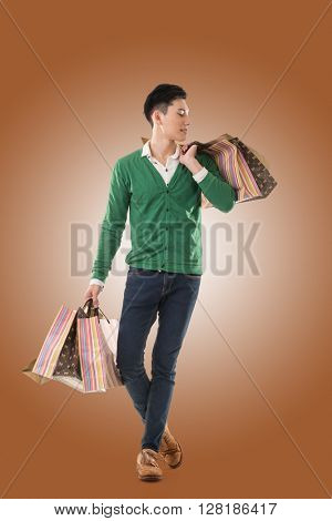 Asian young man holding shopping bags, full length portrait isolated.
