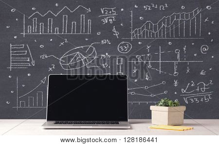 An elegant office desktop with portable laptop and drawn pie charts, graphs, numbers in the background concept