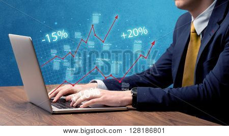 An elegant businessman working on graph statistics calculation using a laptop with clear blue background concept