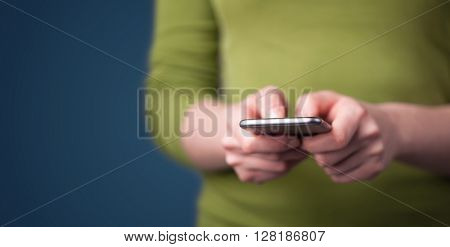 Young woman holding smarthphone in hand while typing