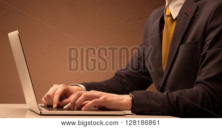 An office worker in elegant suit sitting at desk, typing on portable laptop with empty brown wall background