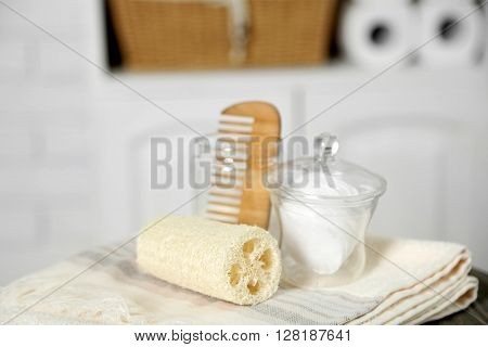 Bathroom set with towels, sponges and comb on stool in light interior