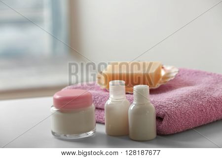 Blue towel with cosmetics and soap on bathroom table