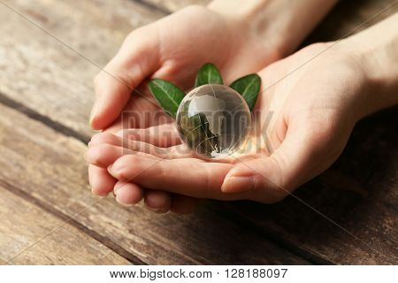Female hands holding small glass globe on wooden table closeup