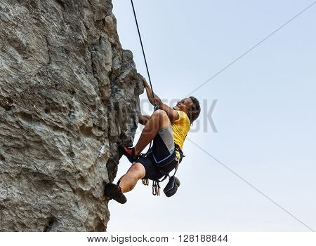 Man is climbing on the rock with harness and rope
