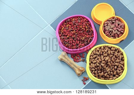 Pet food in  bowls on a floor.