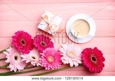 Bouquet of gerbers and present box on pink wooden ackground