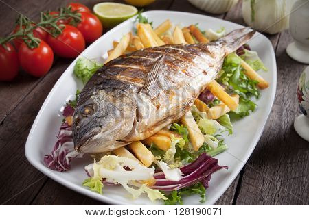Grilled gilt-head bream fish with french fries and salad