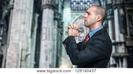Penitent businessman praying in a church