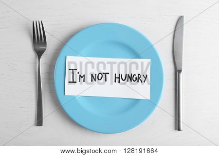 Words I'm not hungry in a plate on white table. Top view.