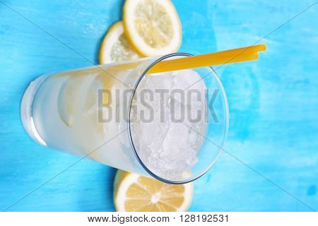 Glass of lemon soda with crushed ice on blue wooden table