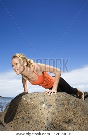 Caucasian young adult woman doing push up on rock.