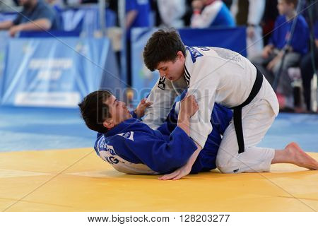 ST. PETERSBURG, RUSSIA - APRIL 16, 2016: Fight Baiaman Sagynbai Uulu of Kyrgyzstan (blue) vs Neil MacDonald of Great Britain during the Junior European Judo Cup
