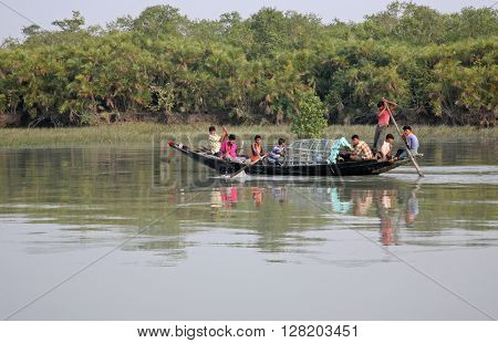 SUNDARBANS, INDIA - JANUARY 15: Wooden boat crosses the Ganges River January 15, 2009 in Sundarbans, West Bengal, India. To use a small wooden is easy, fast and cheap way how to cross the Ganges River