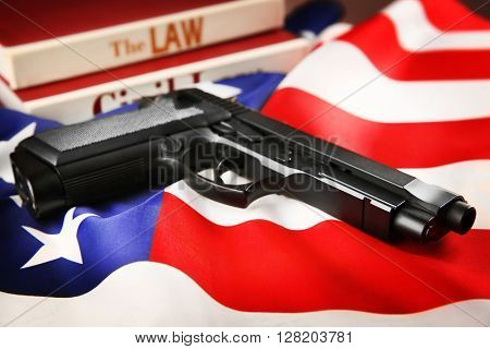 Gun and books of civil law on USA flag background