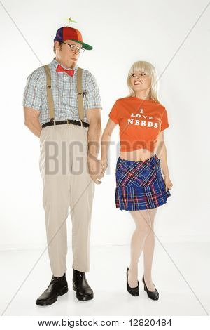 Caucasian young man dressed like nerd wearing propeller hat holding hands with Caucasian blonde young woman wearing tshirt reading I love nerds and plaid skirt.