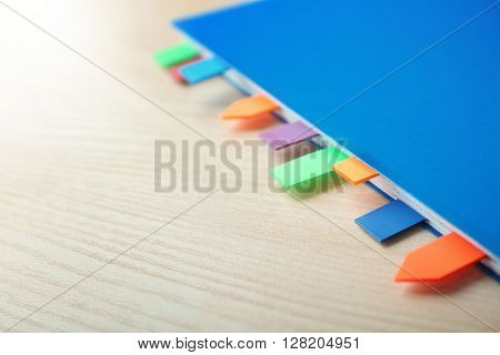Blue notebook with bookmarks on wooden table