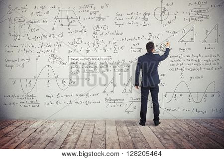 A man in dark business suit is drawing algebraic graphics geometry figures on the white wall and writing down formulas to solve these different mathematical tasks