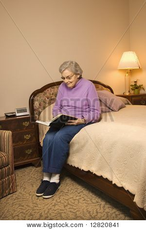 Elderly Caucasian woman in  bedroom at retirement community center reading a book.