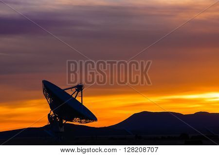 Sunset in the high desert of New Mexico, featuring a radio telescope
