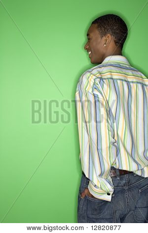 Back view of African-American smiling teen boy with hand in back pocket of jeans standing against green background.