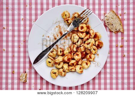 high-angle shot of a plate with remains of tortellini with bolognese sauce and remains of bread, on a table set with a checkered tablecloth
