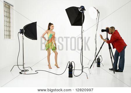 Ung vuxen kvinnlig kaukasiska modell att bli fotograferad i studio av unga vuxna afrikanska amerikanska manliga