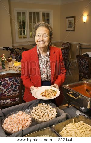 Elderly Caucasian woman at buffet in the dining room of a retirement community center.