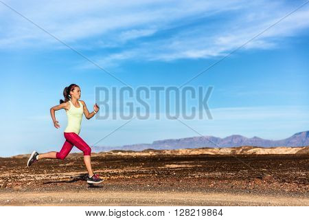 Trail runner female athlete running in nature rocky mountain background. Active fit sports woman in red capris and sportswear sprinting on rocks path working out cardio training body.