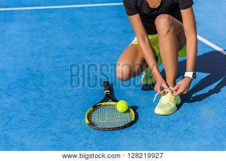 Sports woman athlete getting ready for playing a game of tennis tying laces of her running shoes lacing the shoelaces on outdoor blue hardcourt in summer. Professional player preparing for tournament.