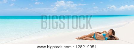 Paradise tropical vacation woman relaxing on perfect white sand beach Caribbean travel destination. Luxury living dreamy getaway Asian skincare model lying down sun tanning in secluded resort.