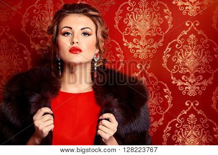 Portrait of a beautiful woman in red dress and luxurious fur coat alluring by vintage wallpaper. Luxury, rich lifestyle. Jewellery. Fashion shot.